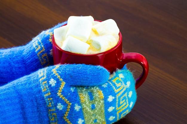 Draufsicht der roten tasse der heißen schokolade und der marshmallows in der weiblichen hand