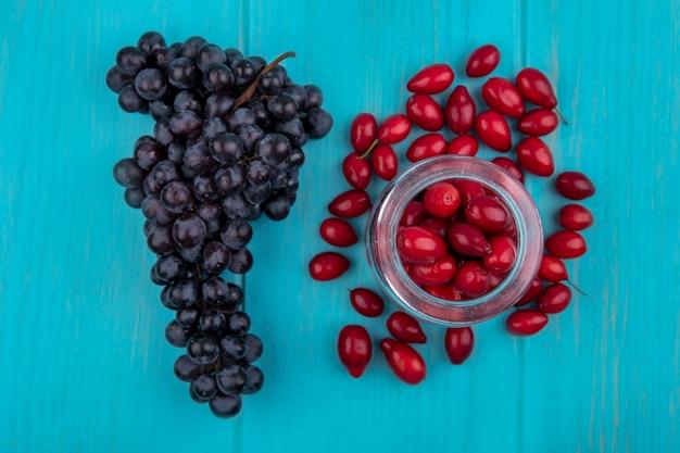 Draufsicht der roten und frischen kornelkirschenbeeren auf dem glasglas mit den schwarzen trauben auf einem blauen hölzernen hintergrund