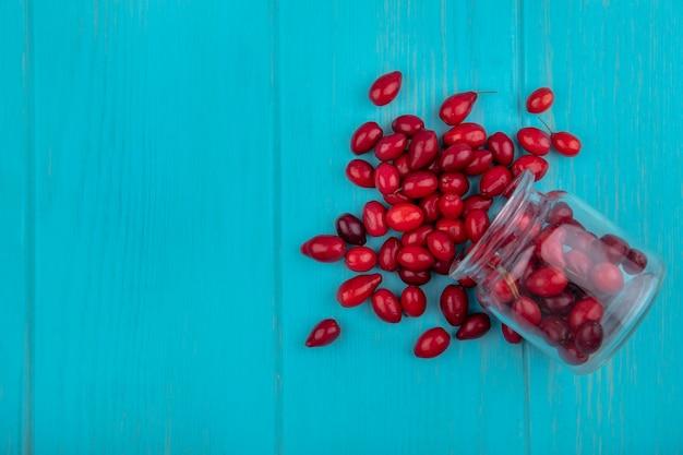 Draufsicht der roten und frischen kornelkirschenbeeren, die aus dem glas auf einem blauen hölzernen hintergrund mit kopienraum herausfallen