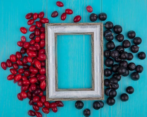Draufsicht der roten und frischen kornelkirschenbeeren und der schwarzen trauben lokalisiert auf einem blauen hölzernen hintergrund mit kopienraum