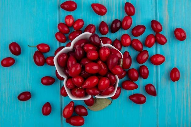 Draufsicht der roten und frischen kornelkirschenfrucht auf einer weißen schüssel auf einem blauen hölzernen hintergrund