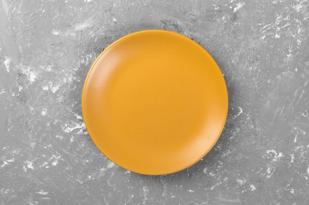Draufsicht der runden leeren gelben mattplatte auf grauem zement