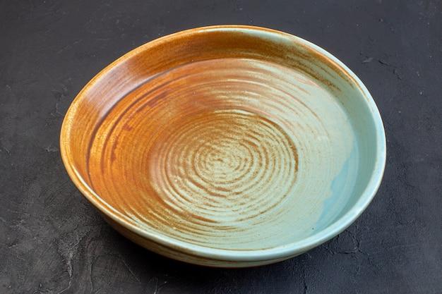 Draufsicht der runden platte in weicher blauer und brauner farbe auf schwarzem hintergrund mit freiem platz