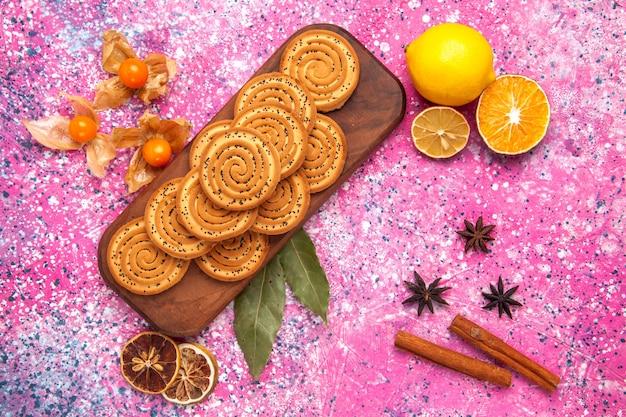 Draufsicht der runden süßen kekse, die mit zimt und zitrone auf rosa oberfläche ausgekleidet sind