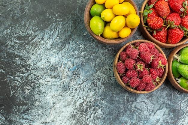 Draufsicht der sammlung von frischen früchten in eimern auf der linken seite auf dunklem hintergrund