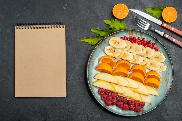 Draufsicht der sammlung von gehackten frischen früchten auf einem blauen teller und besteck neben dem notebook auf schwarzem tisch