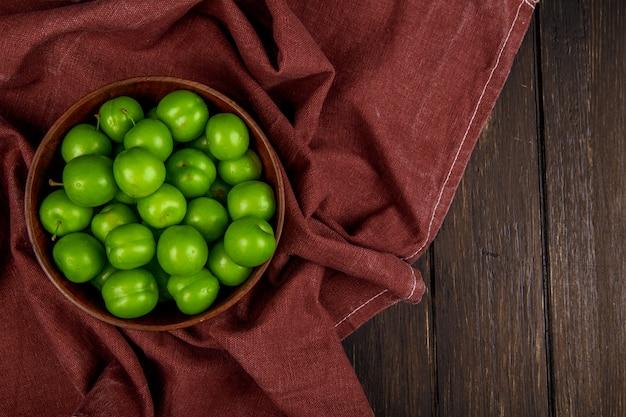 Draufsicht der sauren grünen pflaumen in einer holzschale auf dunklem rustikalem tisch mit kopienraum