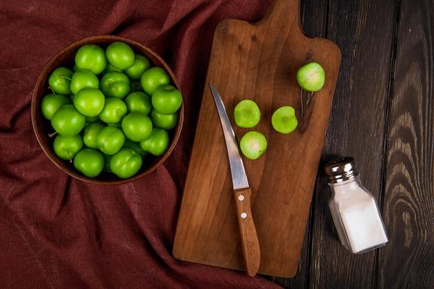 Draufsicht der sauren grünen pflaumen in einer schüssel und in scheiben geschnittenen pflaumen auf einem hölzernen schneidebrett mit messer und einem salzstreuer auf dunklem rustikalem tisch