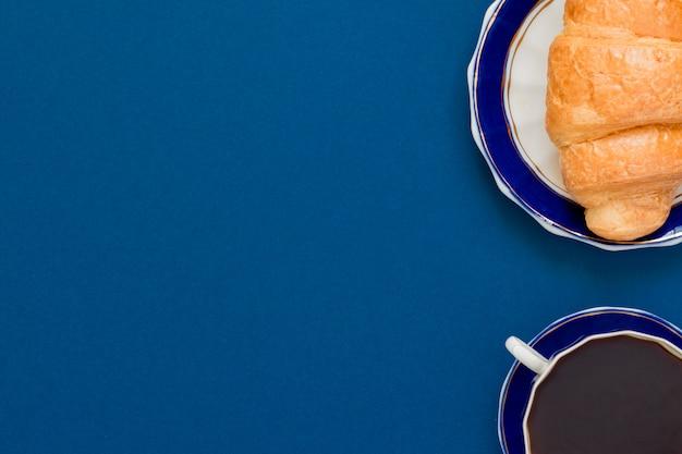 Draufsicht der schale schwarzen coffe und des hörnchens auf einer platte auf blauem hintergrund mit kopienraum. morgenfrühstück im französischen stil.