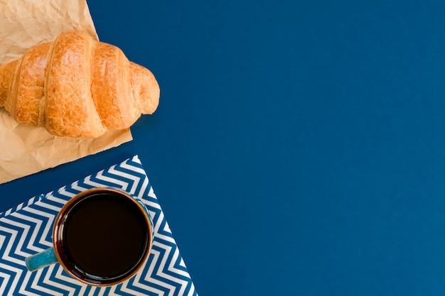 Draufsicht der schale schwarzen coffe und des hörnchens auf kraftpapier auf blauem hintergrund mit kopienraum. morgenfrühstück im französischen stil.