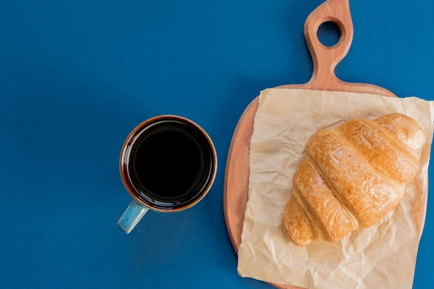 Draufsicht der schale schwarzen kaffees und des hörnchens auf einem schneidebrett und einem kraftpapier