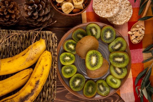 Draufsicht der scheiben der kiwi auf einem teller und bündel der bananen in einem weidenkorb, holzlöffel mit erdnüssen und reiscrackern auf holz