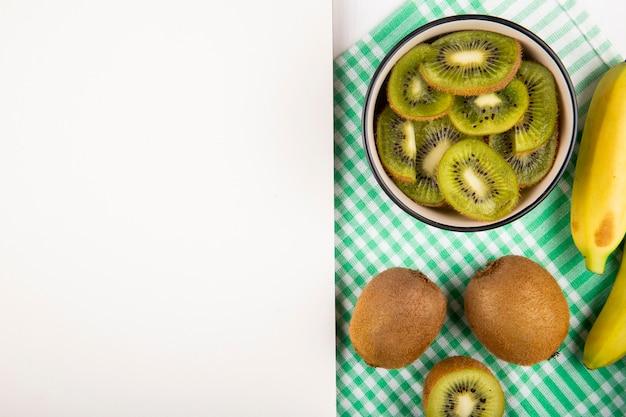 Draufsicht der scheiben der kiwi in einer schüssel und in den frischen reifen bananen auf karierter serviette auf weiß mit kopienraum