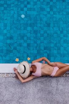 Draufsicht der schlanken frau der passform im bikini am rande des schwimmbades, das urlaub genießt