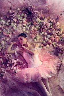 Draufsicht der schönen jungen frau im rosa ballett-tutu, umgeben von blumen