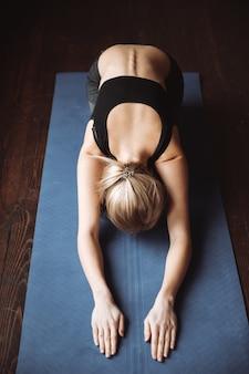 Draufsicht der schönen jungen sportlerin, die yogaübungen macht