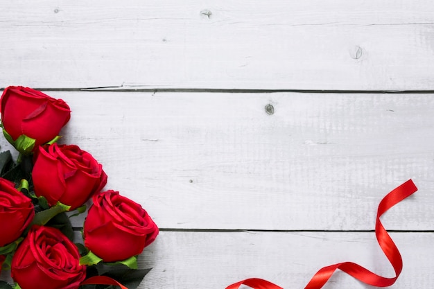 Draufsicht der schönen roten rose und des bandes auf weißem hölzernem hintergrund mit copyspace für valentinstag und liebesthema.