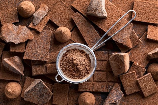 Draufsicht der schokolade mit süßigkeit und sieb