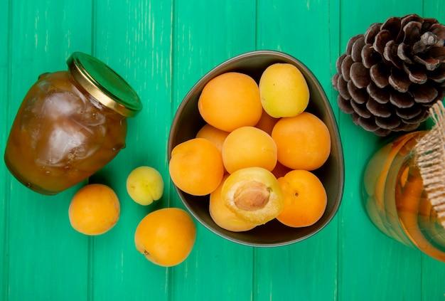Draufsicht der schüssel aprikosen und des glases der pfirsichmarmelade mit kompott und tannenzapfen auf grünem hintergrund