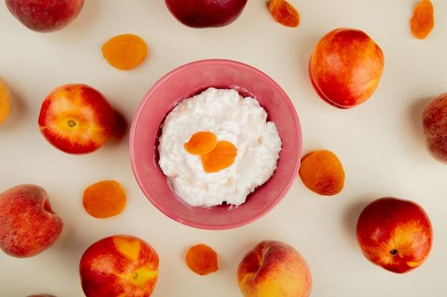 Draufsicht der schüssel des hüttenkäses mit rosinen und pfirsichen herum auf weißer oberfläche