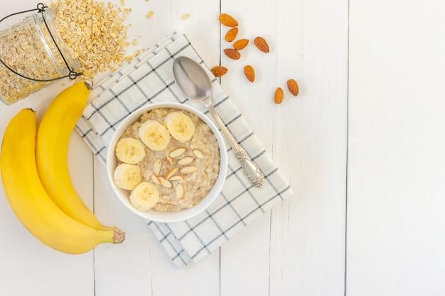 Draufsicht der schüssel haferflocken mit geschnittener bananennahaufnahme auf holztisch.