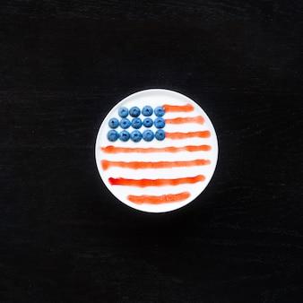 Draufsicht der schüssel mit dem joghurt, stau und blaubeeren, ausgebreitet in der amerikanischen flagge