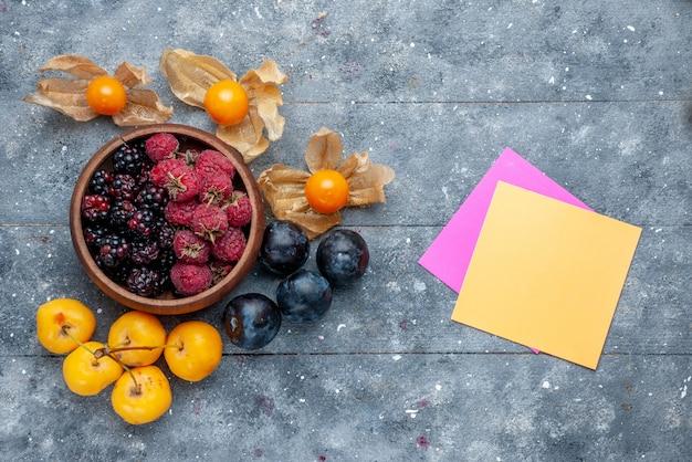Draufsicht der schüssel mit den beeren frische reife früchte mit kirschen und pflaumen auf grauem, frischem wald der beerenfrucht