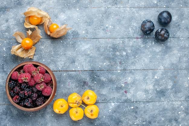 Draufsicht der schüssel mit den frischen reifen früchten der beeren auf dem frischen milden wald der grauen beerenfrucht