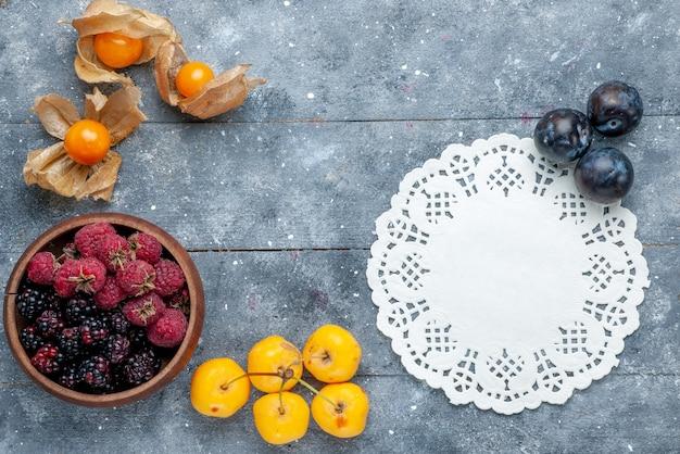 Draufsicht der schüssel mit den frischen und reifen beerenfrüchten auf dem frischen milden wald des grauen rustikalen beerenfruchts