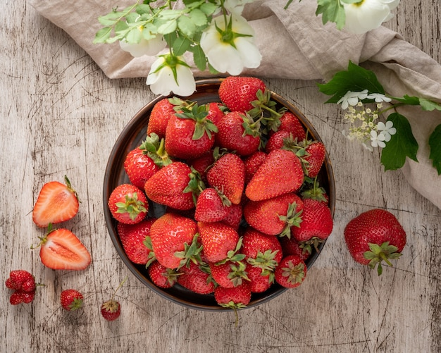 Draufsicht der schüssel mit erdbeere auf holztisch