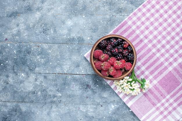Draufsicht der schüssel mit frischen und reifen beerenfrüchten auf grauem, reifem, weichem wald der beerenfrucht