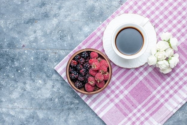 Draufsicht der schüssel mit frischen und reifen beerenfrüchten mit kaffee auf grauem, reifem, weichem wald der beerenfrucht
