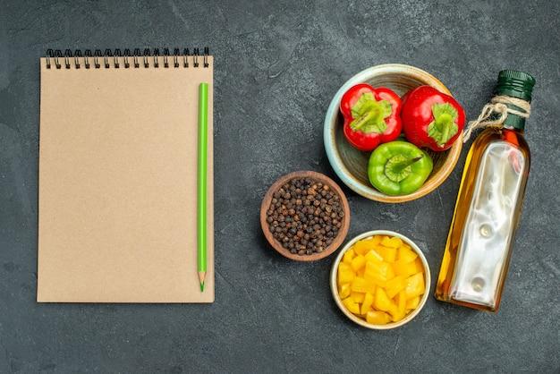 Draufsicht der schüssel paprika auf der rechten seite mit kräuter- und gemüseschalen-ölflasche und notizblock auf der seite auf grünem tisch