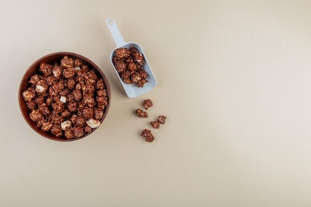 Draufsicht der schüssel und des löffels des schokoladenpopcorns auf der linken seite und der weißen oberfläche mit kopienraum