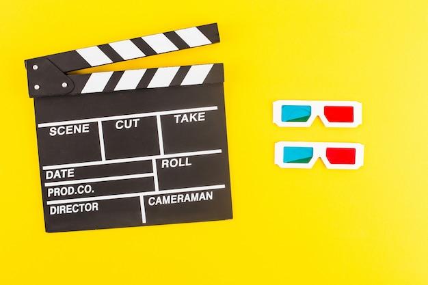 Draufsicht der schwarzen klappe und der 3d-brille lokalisiert auf gelb