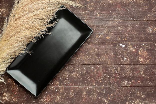 Draufsicht der schwarzen kuchenform auf braunem rustikalem holzholzkuchen Kostenlose Fotos