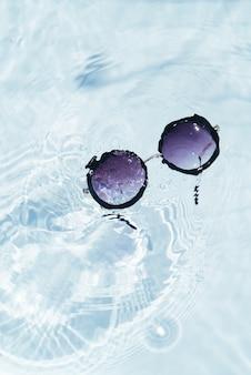 Draufsicht der schwarzen sonnenbrille auf poolwasseroberfläche