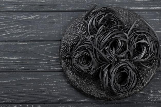 Draufsicht der schwarzen tagliatelle auf platte