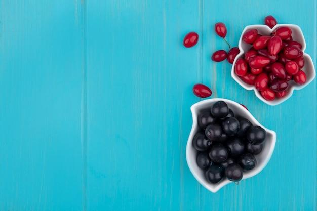 Draufsicht der schwarzen trauben auf einer schüssel mit kornelkirschenbeeren auf einem blauen hölzernen hintergrund mit kopienraum