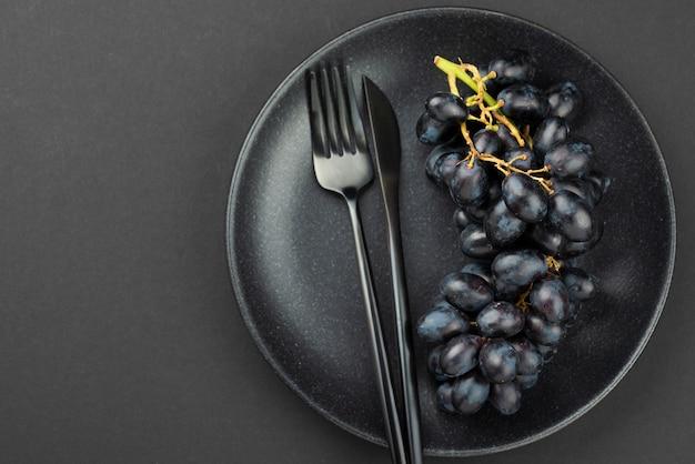 Draufsicht der schwarzen trauben auf platte mit besteck