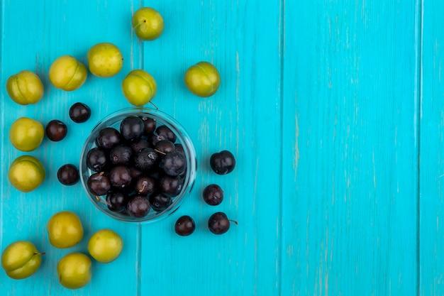 Draufsicht der schwarzen traubenbeeren in der schüssel und im muster von pflaumen und traubenbeeren auf blauem hintergrund mit kopienraum