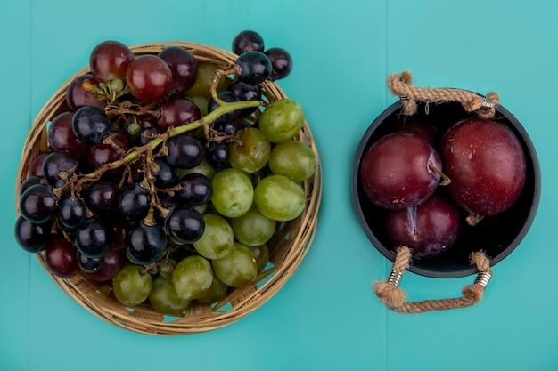 Draufsicht der schwarzen und weißen trauben im korb mit geschmackskönig pluots in der schüssel auf blauem hintergrund