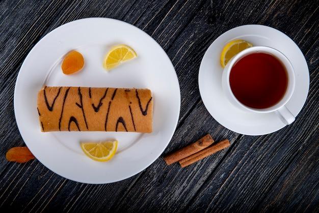 Draufsicht der schweizer rolle mit aprikosenmarmelade auf einem weißen teller, der mit einer tasse tee auf rustikal serviert wird