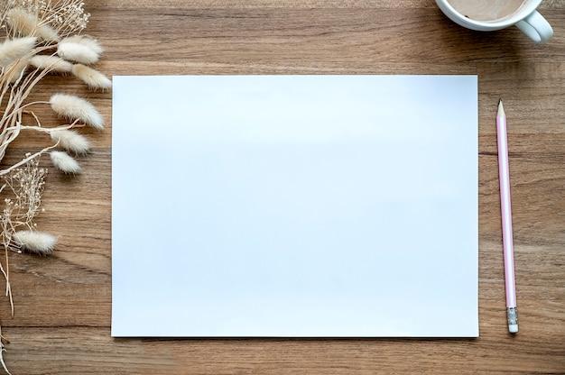 Draufsicht der seite des leeren papiers auf hölzernem hintergrundschreibtisch.