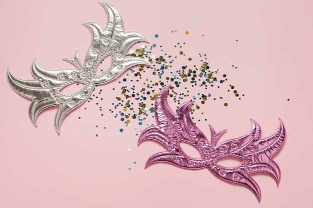 Draufsicht der silbernen und rosa karnevalsmasken
