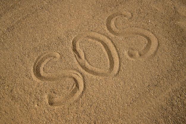 Draufsicht der sos-warnung auf dem braunen sand