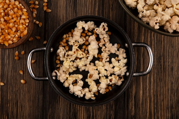 Draufsicht der soßenpfanne mit popcorn mit maiskörnern auf einer holzschale auf einer holzwand