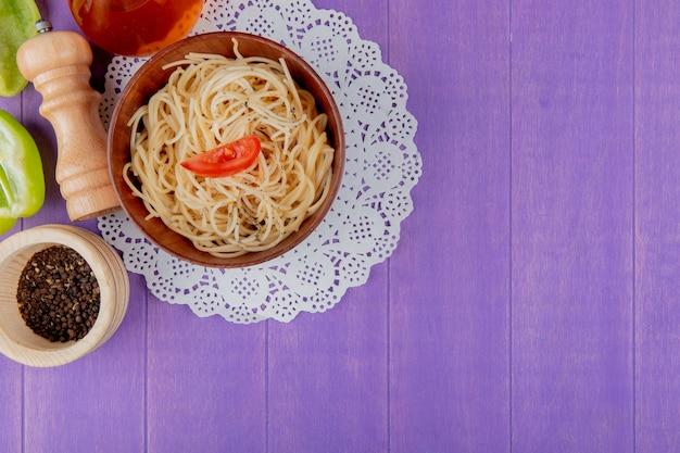 Draufsicht der spaghetti-nudeln in der schüssel auf papierdeckchen mit halb geschnittenem pfefferbuttersalz und schwarzen pfeffersamen auf lila hintergrund mit kopienraum