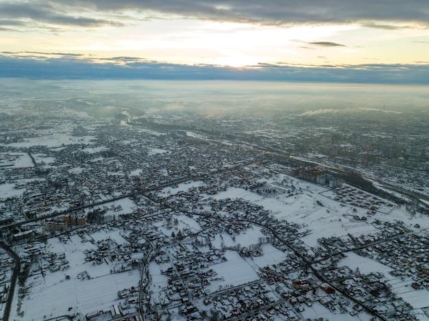 Draufsicht der stadtvororte oder der netten häuser der kleinen stadt am wintermorgen auf bewölktem himmelhintergrund. konzept der luftdrohnenfotografie.