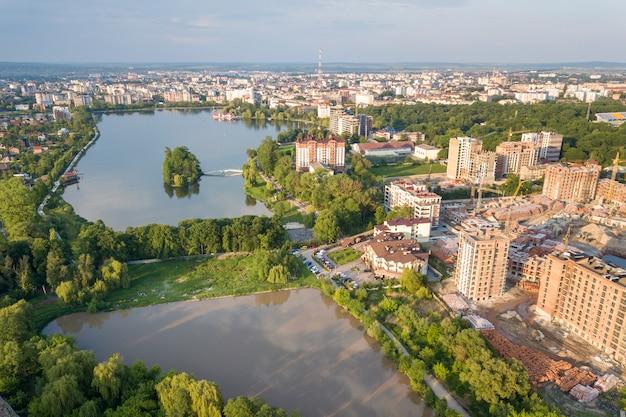 Draufsicht der städtischen sich entwickelnden stadtlandschaft mit hohen wohngebäuden und vororthäusern. luftaufnahmen mit drohnen.